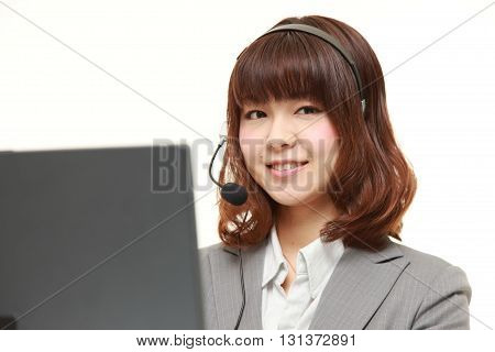 studio shot of young Japanese businesswoman of call center with head sets on white background