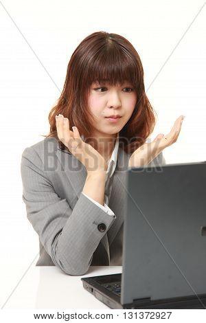 studio shot of young Japanese businesswoman shocked on white background