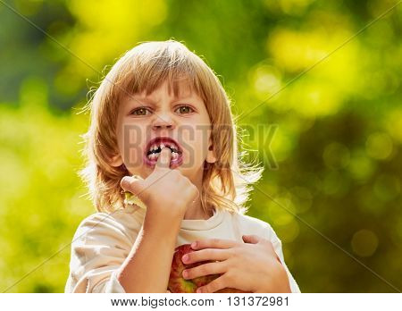 portrait of little handsome boy clasps apples by hands, He is pointing at the fallen teeth,  outdoor summer autumn warm