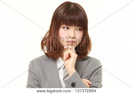 studio shot of young Japanese businesswoman worries about something on white background