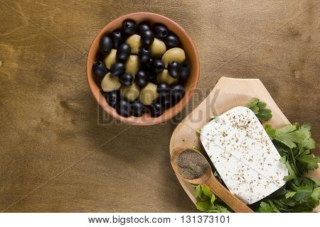 Feta cheese and fresh herbs in a wooden plate and green olives on the table
