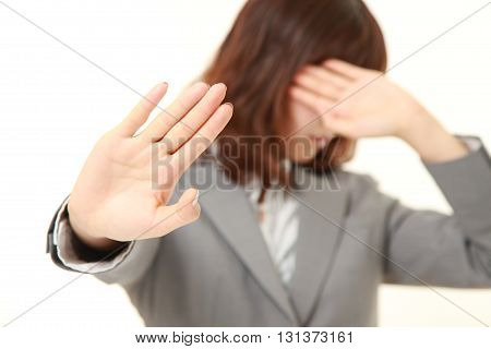 studio shot of young Japanese businesswoman making stop gesture on white background