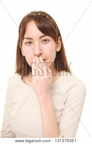 studio shot of woman making the speak no evil gesture
