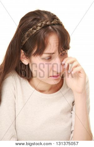 studio shot of young woman cries on white background