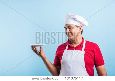 Portrait of handsome Indian male chef in uniform presenting an empty plate and smiling, standing isolated over plain blue background, with copy space