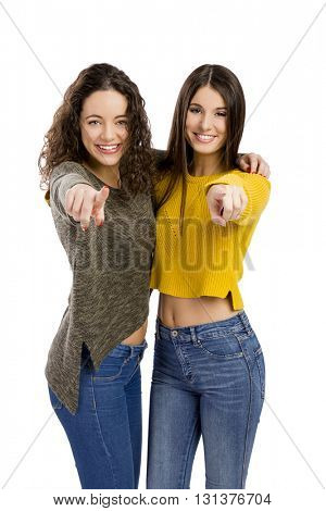 Studio portrait of two beautiful girls pointing and looking to the camera