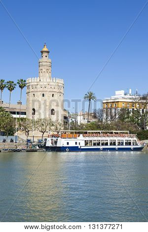 Ancient lighthouse Torre del Oro at Seville, tourist boat at the pier