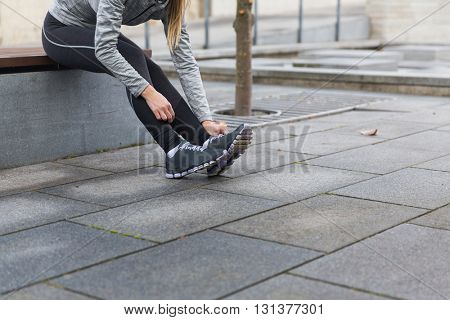 fitness, sport, people and lifestyle concept - close up of young sporty woman tying shoes outdoors