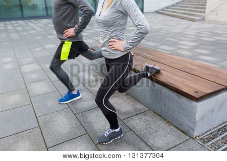 fitness, sport, people, exercising and lifestyle concept - close up of couple couple doing lunge exercise on city street