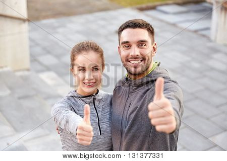 fitness, sport, people and gesture concept - smiling couple outdoors showing thumbs up on city street stairs