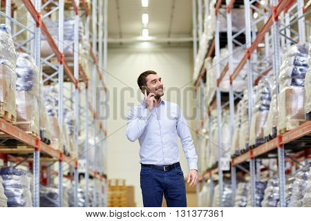 wholesale, logistic, business, export and people concept - smiling businessman calling on smartphone at warehouse