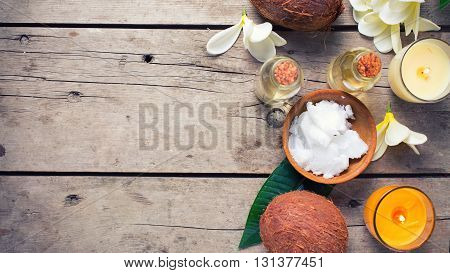 Coconuts and coconut oil on vintage wooden background. Selective focus. Flat lay. Natural organic spa products. Place for text. Toned image.