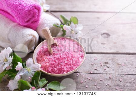 Spa or wellness organic product. Pink sea salt in bowl towels and apple tree flowers in ray of light on aged wooden background. Selective focus.