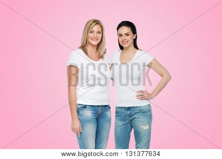 friendship, diverse, body positive and people concept - group of happy different women in white t-shirts hugging over pink background