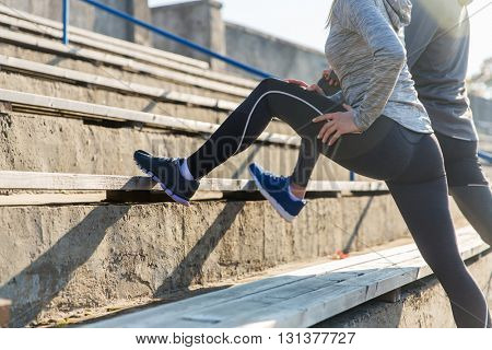 fitness, sport, exercising and lifestyle concept - close up of couple stretching leg on stands of stadium