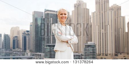 business and people concept - young smiling businesswoman with crossed arms over dubai city background