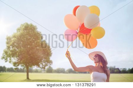 happiness, summer, holidays and people concept - smiling young woman wearing sunglasses with balloons over summer park background