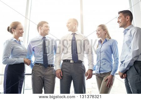 business, teamwork, people and technology concept - smiling business team meeting and talking in office