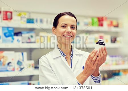 medicine, pharmaceutics, health care and people concept - happy female pharmacist with drug jar at pharmacy
