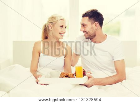 people, love, care and happiness concept - happy couple having breakfast in bed at home