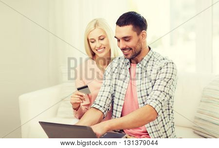 technology, people, e-money and commerce concept - smiling happy couple with laptop computer and credit or bank card shopping online at home
