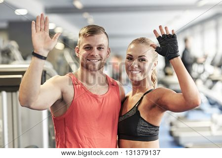 sport, fitness, lifestyle, gesture and people concept - smiling man and woman waving hands in gym