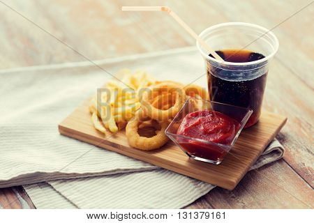 fast food and unhealthy eating concept - close up of deep-fried squid rings, french fries, cola and ketchup on wooden table