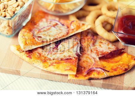 fast food, italian kitchen and eating concept - close up of pizza and other snacks on wooden table