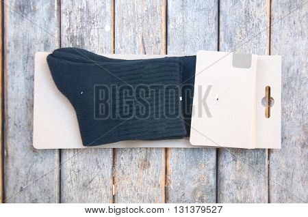Black socks in packing on wood table