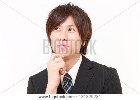 studio shot of young Japanese businessman thinks about something on white background