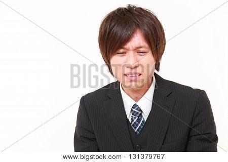 studio shot of sad young Japanese businessman on white background