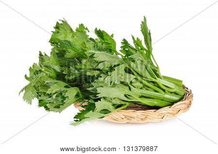 fresh celery in rattan basket on white background