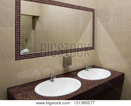 A room with a sink in a public restroom