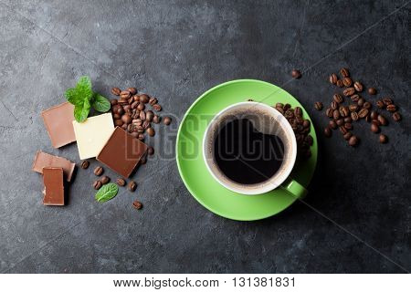 Chocolate and coffee cup on dark stone table. Top view