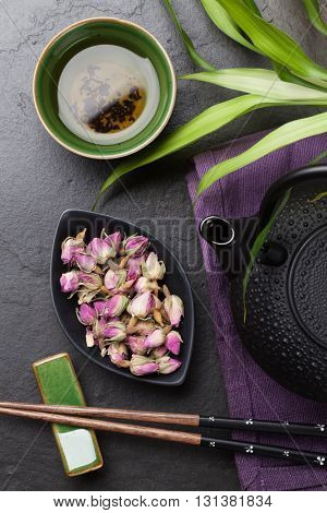 Asian sushi chopsticks, rose tea and teapot over stone table