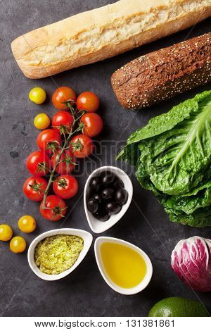 Cooking food ingredients. Lettuce salad, avocado, olives, cheese, bread and tomato cherry over stone background. Top view