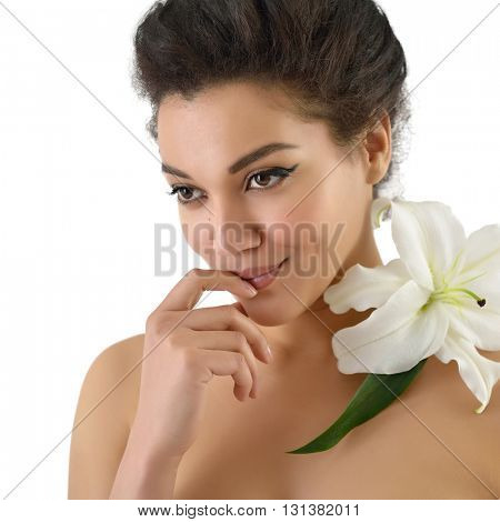 Beauty portrait of young mulatto woman with lily flower over white background.