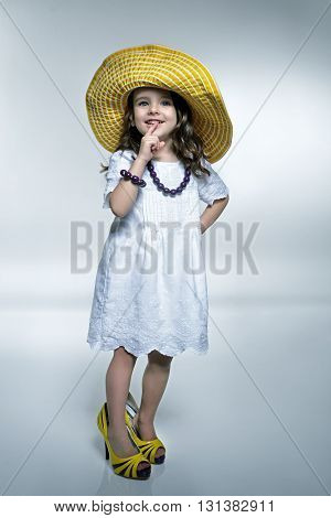 Little fashionista. Little beautiful fashion girl posing white dress, mother's high heels shoes and panama hat. Summer fashion.