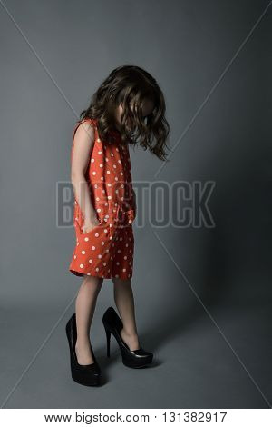 Little fashionista. Little beautiful fashion girl posing in mother's high heels shoes and happy smiling.
