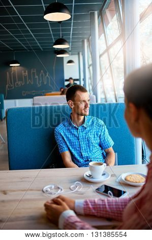joyful smiling man sitting in a cafe opposite the woman at a table made of wood and holds a smart phone with headphones. in the background a bright window with bright daylight. cup of coffe on the table