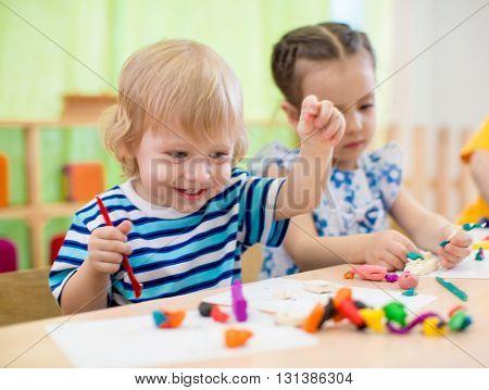 Happy children doing arts and crafts. Kids in kindergarten.