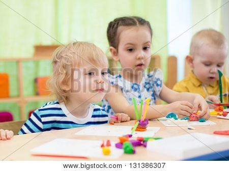 kids modeling or playing in kindergarten with interest. Children in day care centre.