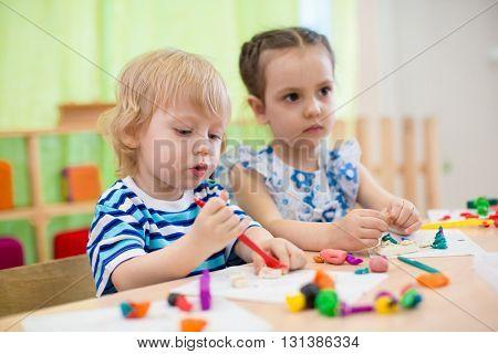 Kids doing arts and crafts. Children in kindergarten.