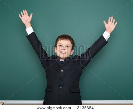 school boy in black suit open arms on green chalkboard background, education concept