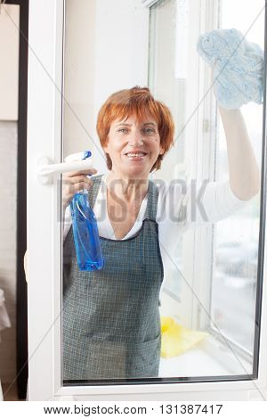 Mature woman cleaning window. Female washing window
