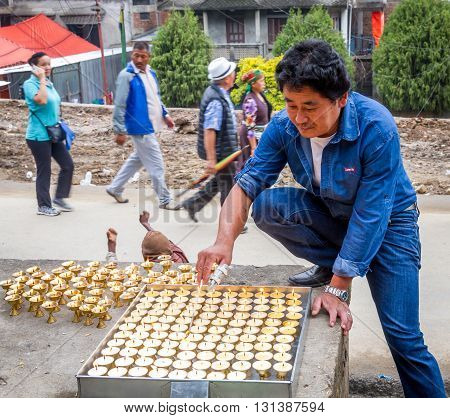 kathmanduNepal - May 21 2016 : A buddhist man is lighting Yak butter lamps on 2560th Buddha Jayanti or Buddha Day.