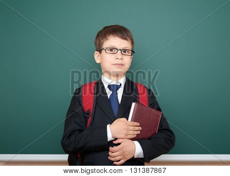 school boy portrait in black suit on green chalkboard background with red backpack and book, education concept