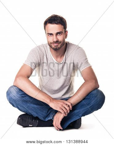 Casual young man sitting on the floor with his legs crossed isolated on white
