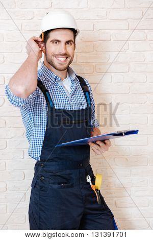 Smiling young lead worker taking notes on his clipboard while working