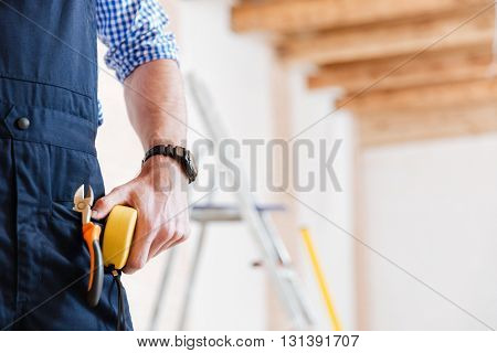 Cropped image of a handyman holding yellow tape measure in his hand